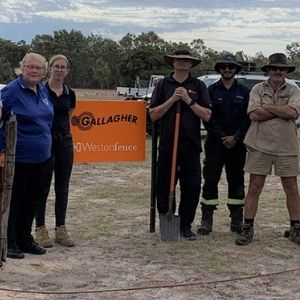Group of landcarers standing along Gallagher signage