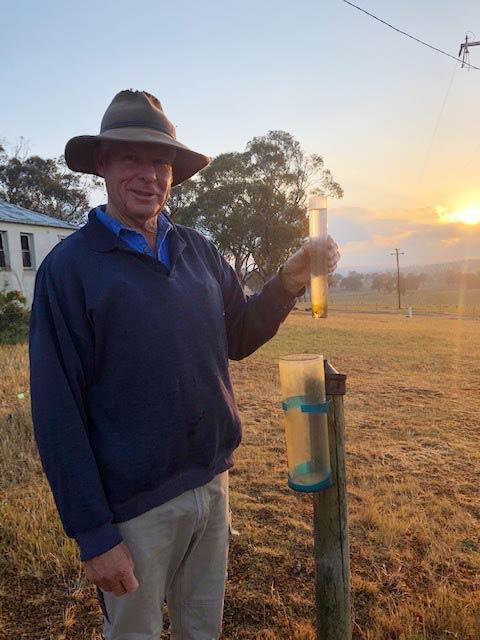 Landowner holding an almost full rainfall gauge